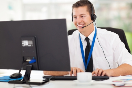 helpdesk: handsome technical support operator working on computer Stock Photo