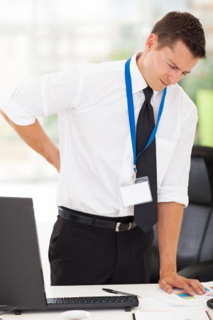 exhausted: businessman having lower back pain in office Stock Photo