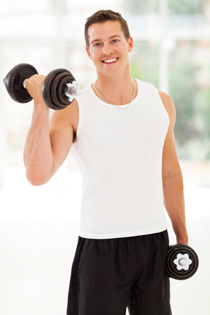 happy young man training with dumbbells at the gym photo