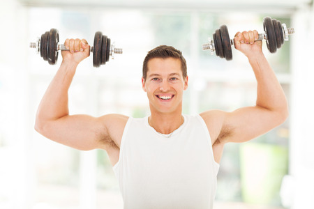 smile close up: healthy young man lifting two dumbbells