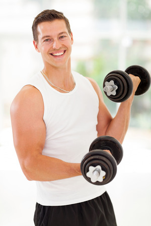 man working out: portrait of fitness young man at the gym doing exercises
