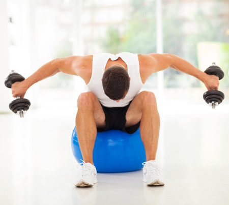 fitness man exercising with dumbbells sitting on gym ball photo