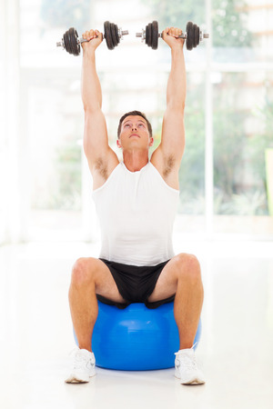 healthy man lifting up a dumbbells seated on fitness ball photo