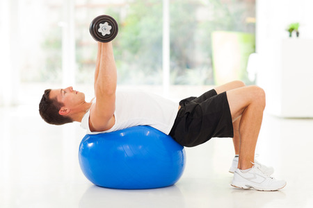 young man training with dumbbells lying on a fitness ball photo