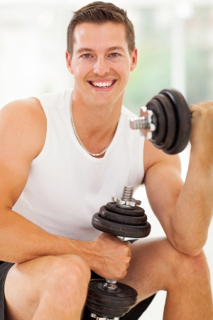 cheerful young man working out with dumbbells in gym photo