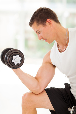 healthy young athlete lifting weights in the gym photo