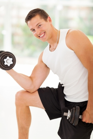 attractive muscular man lifting weights photo
