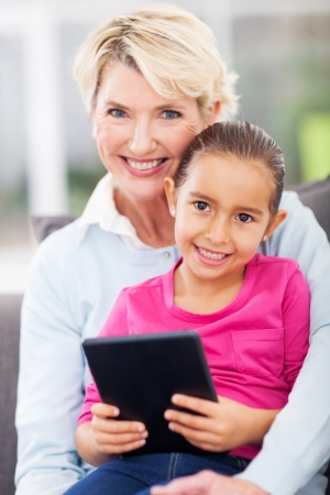 cute little granddaughter and grandmother with tablet pc at home photo