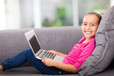cheerful little girl with a laptop computer lying on couch photo