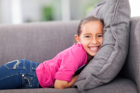 beautiful little girl lying on a couch with a tablet pc photo