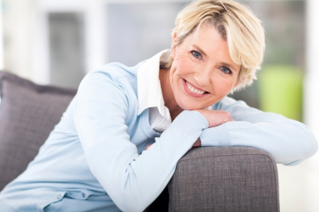 woman mature: pretty senior woman relaxing on a couch at home