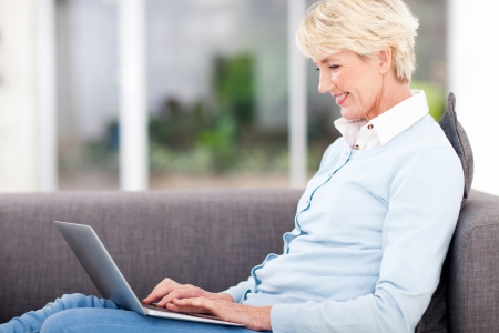 woman couch: happy elderly woman using laptop computer at home