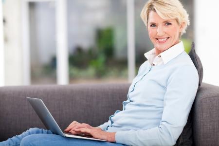 pretty senior woman at home using laptop photo