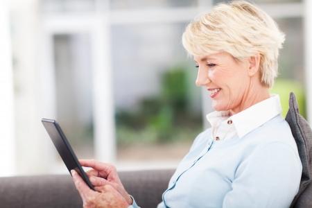 m�s viejo: bastante altos mujer con tablet PC en casa Foto de archivo