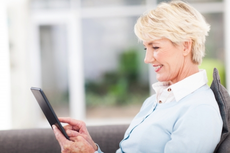 pretty senior woman using tablet computer at home photo