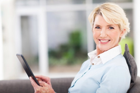 elegant middle aged woman using tablet pc at home photo