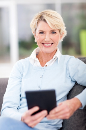 older age: modern senior woman with tablet computer at home