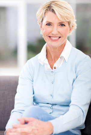 femmes souriantes: belle femme �g�e assise � la maison Banque d'images