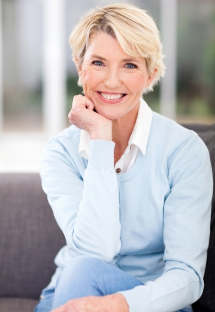 older women: beautiful middle aged woman sitting at home Stock Photo