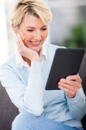 attractive mature woman reading a book on tablet computer photo