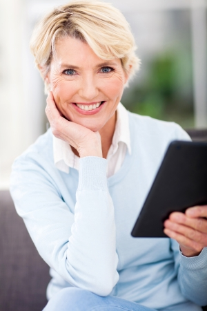 happy middle aged woman holding tablet pc at home photo