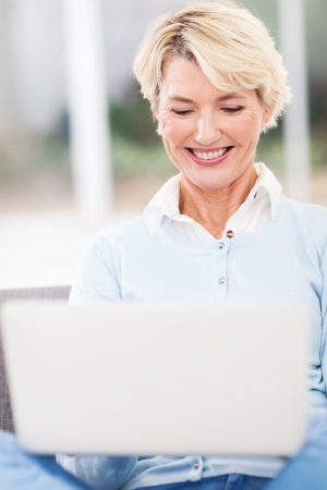 mid age: cheerful mid age woman using laptop computer at home Stock Photo