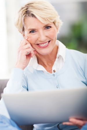 attractive middle aged woman with laptop computer and looking at the camera photo