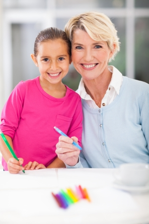 happy little girl with her grandmother drawing at home Stock Photo - 22889896