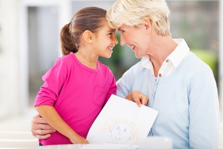 loving little girl giving her grandmother a picture she drew Stock Photo - 22889899