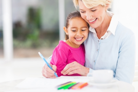 happy senior grandmother teaching her granddaughter how to draw at home photo