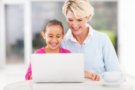 cute little girl and granny using laptop at home photo