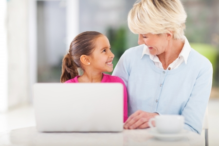 cheerful little girl and grandma using laptop computer at home photo