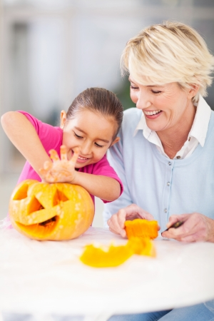 excited little girl cleaning her halloween pumpkin with granny at home Stock Photo
