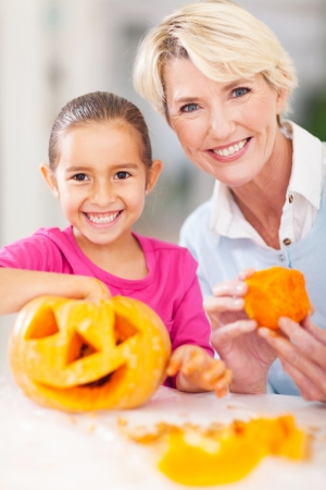 cheerful grandmother and her granddaughter making halloween pumpkin at home photo