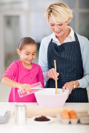 happy grandmother and granddaughter baking cookies together at home photo