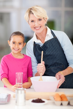 happy granddaughter baking with grandmother at home photo