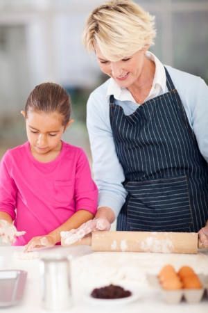 cute grandmother and granddaughter making cookies in kitchen photo