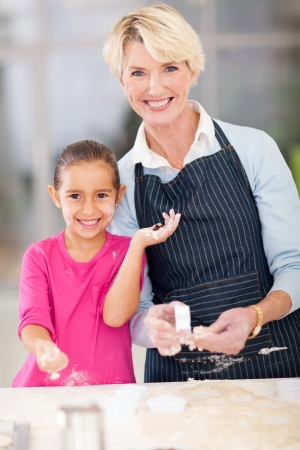 portrait of little girl and senior grandmother baking at home photo