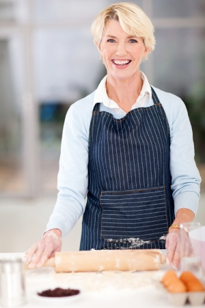smiling middle aged woman baking in kitchen photo