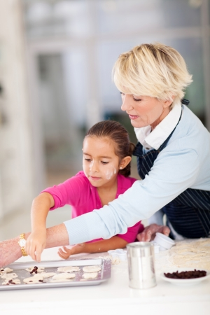 pretty little girl with grandmother baking cookies together at home photo