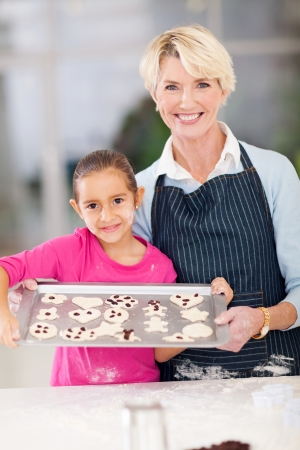 grandmother and granddaughter holding tray of homemade cookies to be baked photo