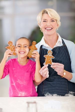 happy little girl and grandmother holding just baked gingerbread cookies in kitchen photo