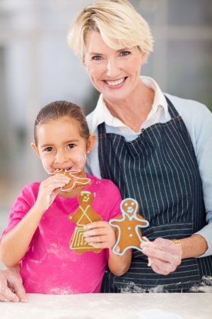beautiful little girl eating gingerbread cookie her grandma just baked photo