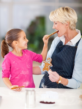 cute little girl feeding just baked gingerbread cookies to her grandmother photo