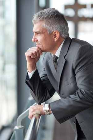 senior businessman: thoughtful senior businessman looking out the window Stock Photo