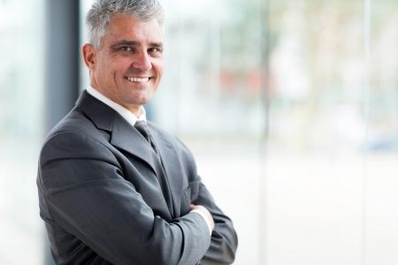 empresarial: hombre de negocios alegre con los brazos cruzados mirando a la cámara
