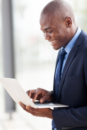 navy blue suit: smiling young african american businessman using laptop computer indoors