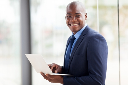 african businessman: handsome african american businessman with laptop in office