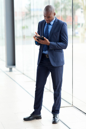 navy blue suit: successful african businessman using tablet computer