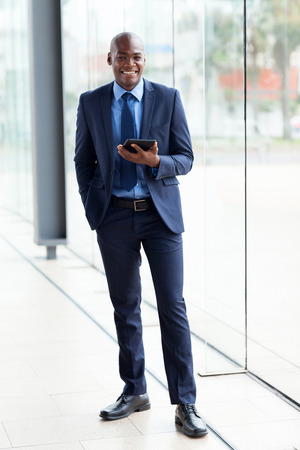 navy blue suit: portrait of african american corporate worker holding tablet computer